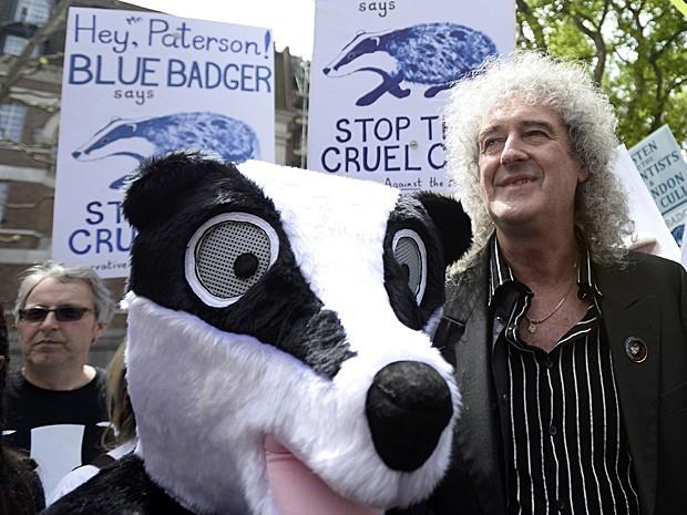 O guitarrista do Queen, Brian May, liderou um protesto contra o sacrifício de texugos, no centro de Londres, no sábado (1º). Ao lado dele, um mascote do animal participou da manifestação (Foto: Dylan Martinez/Reuters)